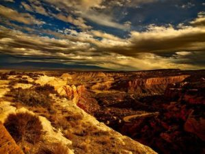 view of a canyon and partly cloudy sky in red and blue tones